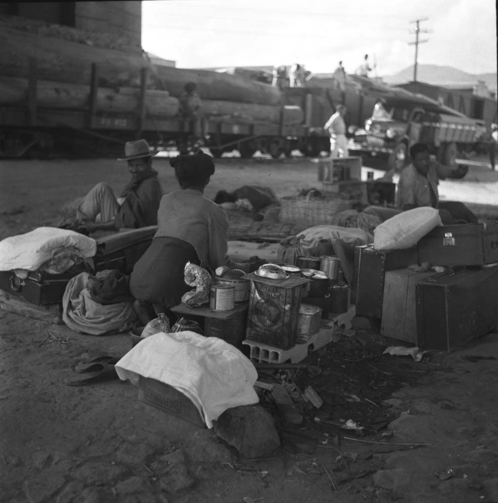 Moradores de rua perto de linha ferroviária com vagões de tora de madeira. Maio de 1955
